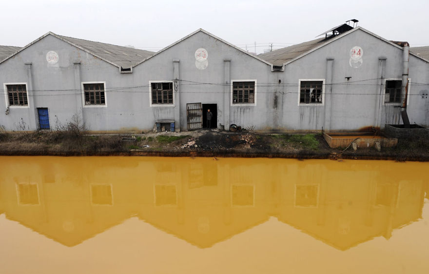 A worker looks at a photographer from a door of a factory manufacturing screws and nuts next to a polluted river in Jiaxing
