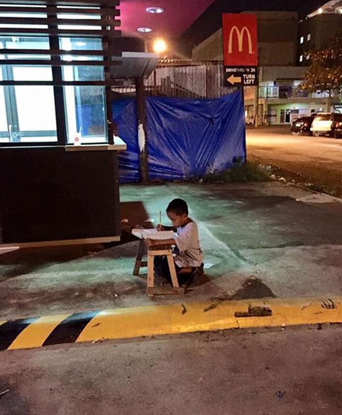 Este niño indigente hace los deberes en la calle a la luz de un McDonalds