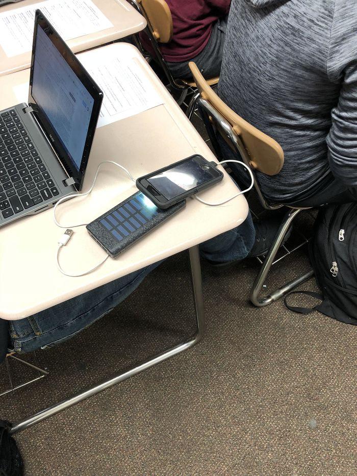 Está Usando La Linterna Del Móvil Para Cargar Una Batería Solar Portátil Y Poder Cargar Su Móvil